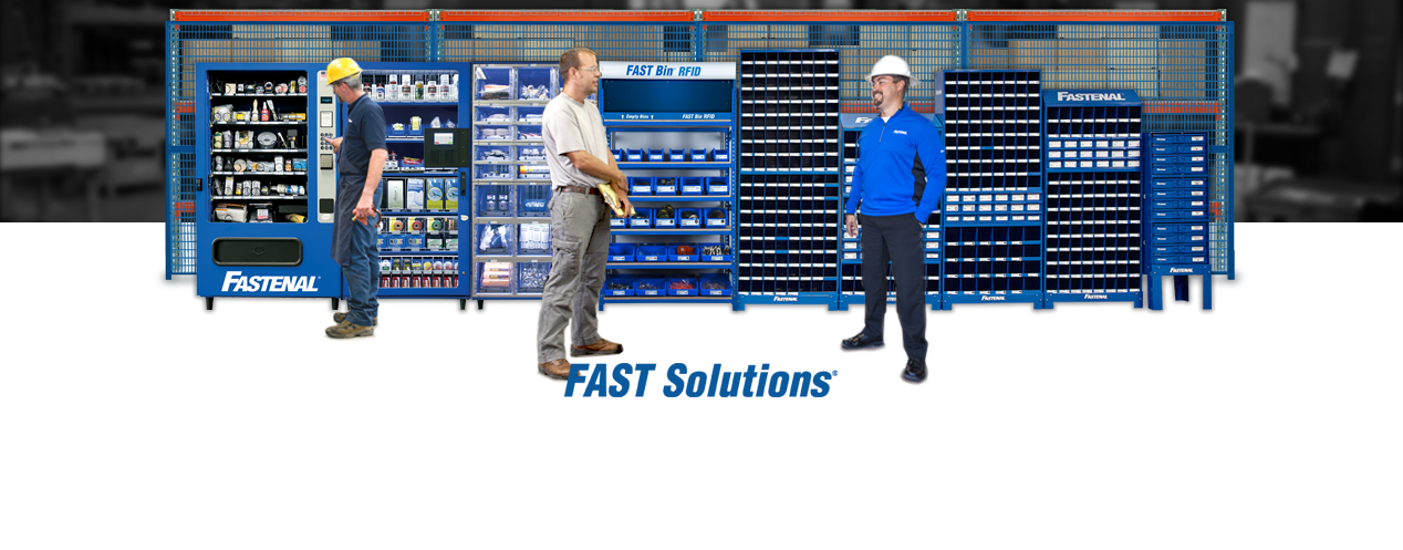 Solution FAST sur place. Rangée de distributeurs automatiques Fastenal bordant le mur. Un homme se procure un produit pendant que deux hommes parlent.